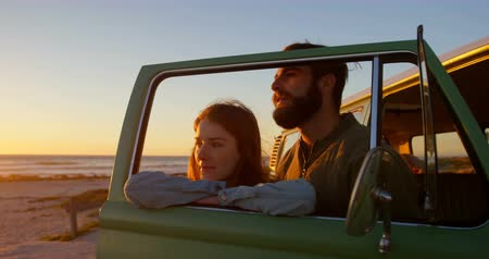 čelo : Young couple standing by van window during sunset on beach. Man kissing woman forehead 4k Dostupné videozáznamy