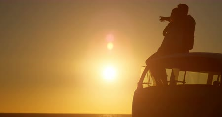 tartózkodás : Silhouette of romantic couple sitting on roof of van. Beautiful sunset in background 4k