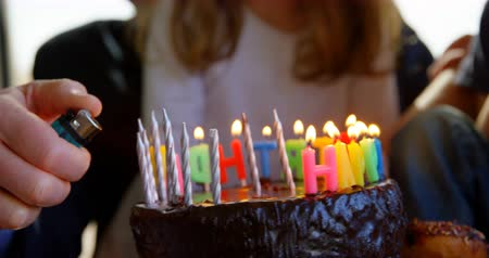 avó : Close-up of grandfather lighting candles on birthday cake. Birthday cake is rotating 4k Vídeos