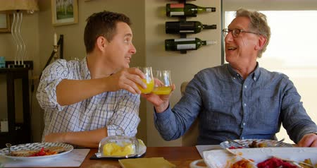 active ageing : Happy father and son toasting glasses of juice at home. Sitting on dining table with food 4k