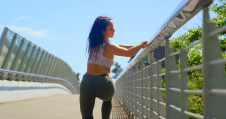 vyvažování : Beautiful young dancer practicing dance on the bridge in the city. Blue sky in the background 4k Dostupné videozáznamy