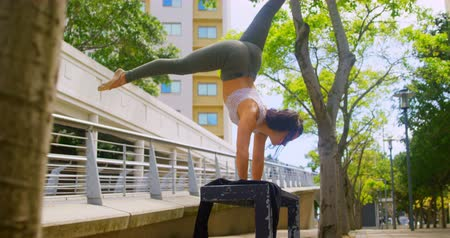 kiegyensúlyozó : Young female dancer practicing handstand on the bench. Bridge and building in the background 4k