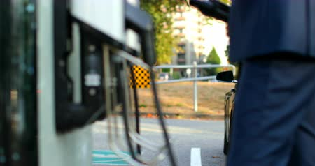 electric vehicle : Businessman charging electric car at charging station. Charge point on the background 4k Stock Footage