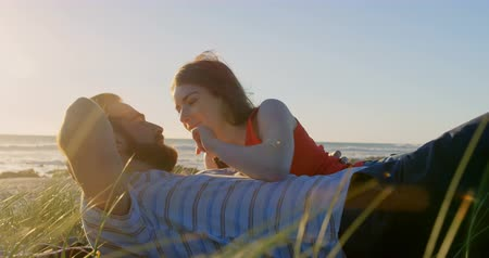 acariciando : Happy beautiful woman touching mans nose on beach. Couple romancing and relaxing on beach 4k