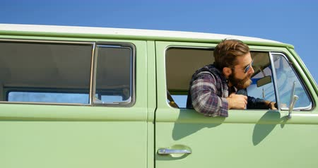 side window : Young stylish man looking through van window. Blue sky in background 4k Stock Footage