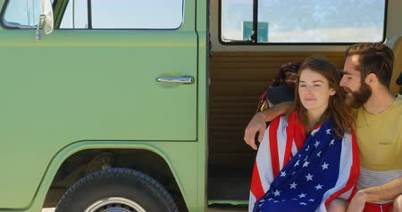 front national : Young couple interacting with each other in van on a sunny day. Woman wrapped in the american flag 4k