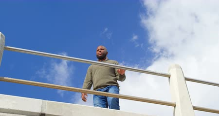 cuarto : Low angle view of man standing near railings. Sky and cloud in the background 4k Archivo de Video