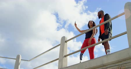 korkuluk : Couple taking selfie with mobile phone near railing. Beautiful sky and cloud in the background 4k Stok Video