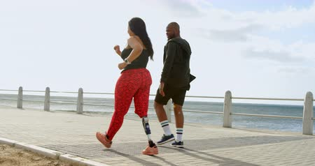 handicap : Couple walking on the promenade near beach. Beautiful sky and sea in the background 4k