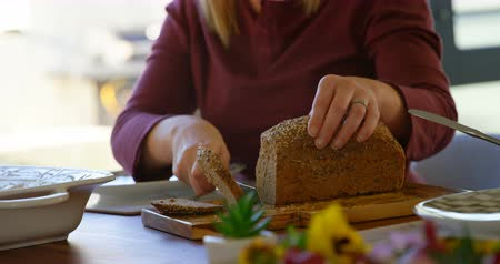 ev gibi : Mid section of woman cutting loaf of bread on dining table. Woman preparing food 4k