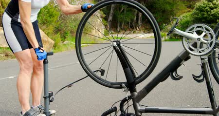 air pump : Middle age athlete pumping a bicycle tire with bike pump on country road. Mountain and tree on background 4k Stock Footage