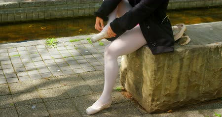 sapatos de salto alto : Low section of female ballerina wearing ballet shoe in the park. Female ballerina sitting on stone bench 4k