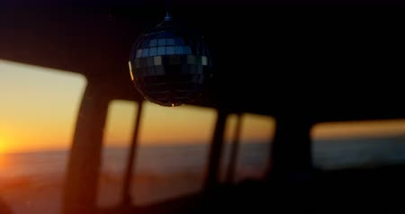 фургон : Close-up of mirror ball hanging in van. Sunset in background 4k
