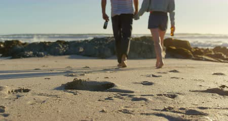 kalmak : Couple holding hands with beer bottle walking on beach. Footprints in the sand 4k