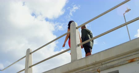 amputee : Low angle view of couple interacting with each other while walking near railing. Sky and cloud in the background 4k
