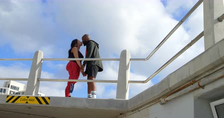 amputee : Side view of couple kissing at promenade near railing. Beautiful sky and cloud in the background 4k