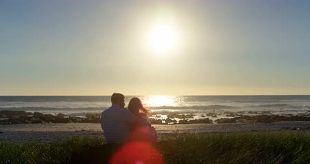 kalmak : Rear view of romantic couple sitting at beach. Beautiful bright sun at beach 4k