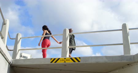amputee : Couple walking with hand in hand near railing on a sunny day. Beautiful sky and cloud in the background 4k