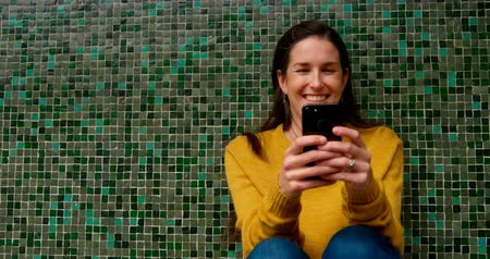 discar : Smiling brunette woman sending text message against green mosaic patterned wall and laughing 4k Stock Footage