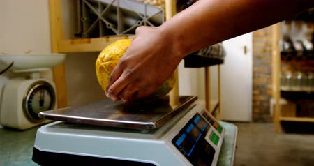 weighing machine : Male staff weighing papaya on weighing machine. Mid section of male staff in supermarket 4k Stock Footage
