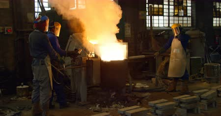 加熱 : Worker melting metal in foundry workshop. Melting metal in container 4k