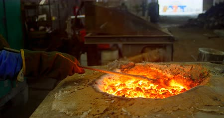 加熱 : Worker melting molten in furnace at foundry workshop. Worker working in foundry workshop 4k