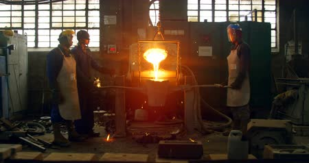 erimiş : Workers melting metal in foundry workshop. Melting metal in container 4k Stok Video
