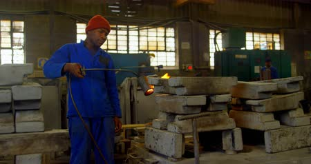 metal casting : Worker heating metal mold with blow torch in foundry workshop. Worker working in foundry workshop 4k