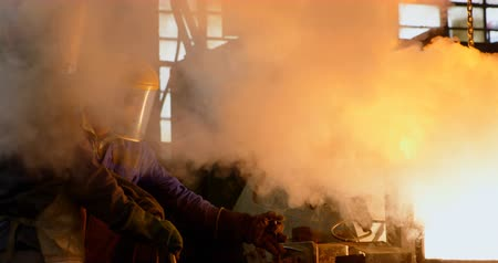 fornalha : Worker melting molten in container at foundry workshop. Worker working in foundry workshop 4k