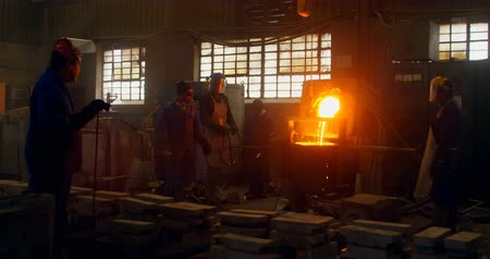metal casting : Workers melting metal in foundry workshop. Melting metal in container 4k Stock Footage