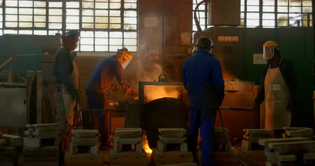 olvasztott : Workers melting metal in foundry workshop. Melting metal in container 4k Stock mozgókép