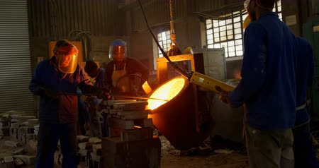 odaklanma : Group of workers pouring molten metal in mold at workshop. Workers working together 4k Stok Video