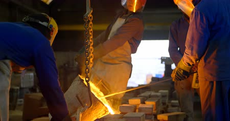 加熱 : Group of workers pouring molten metal in mold at workshop. Workers working together 4k 動画素材