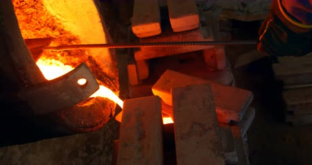 внимательный : Male worker pouring molten metal in mold at workshop. Molten metal in container 4k
