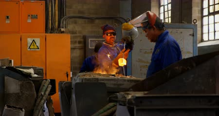 metal casting : Male worker removing molten metal from furnace in workshop. Hot furnace in workshop 4k