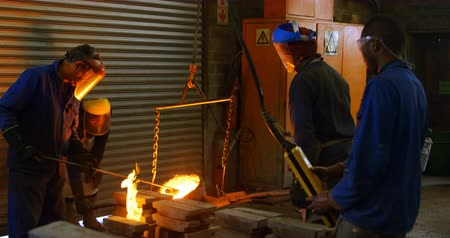 metal casting : Group of workers pouring molten metal in mold at workshop. Workers working together 4k Stock Footage