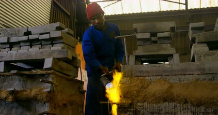 metal casting : Male worker heating mold in workshop. Mlae worker holding blow torch 4k