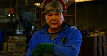 comprimento total : Male worker standing in helmet at workshop. Male worker holding metal rod 4k