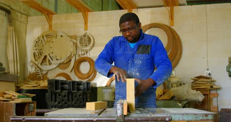 metal casting : Male working on wooden block in workshop. Various wooden equipment in background 4k
