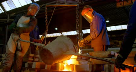 öntvény : Group of workers pouring molten metal in mold at workshop. Workers working together 4k Stock mozgókép