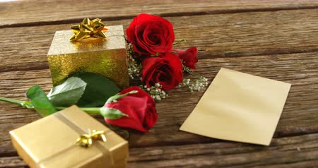 luty : Red roses, gift boxes and card on a wooden surface. Bouquet of red roses around the gift box 4k