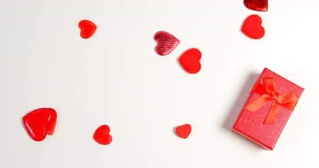 luty : Red gift box and red hearts on white surface. Valentines day concept 4k