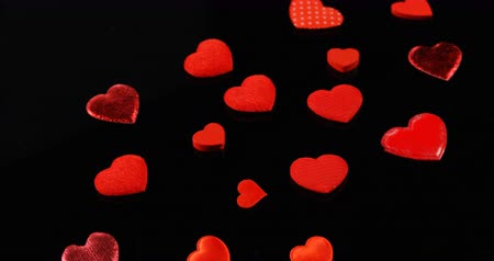 luty : Red hearts shapes falling on the black surface. Valentines day concept 4k