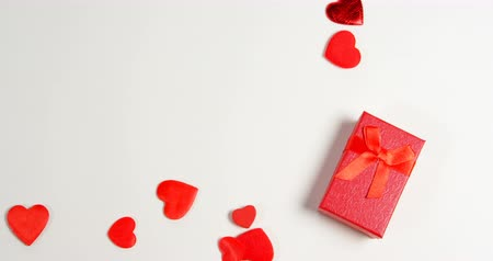 geordend : Red gift box and red hearts on white surface. Valentines day concept 4k