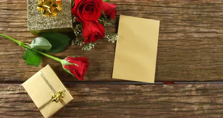 koperta : Red roses, gift boxes and card on a wooden surface. Bouquet of red roses around the gift box 4k