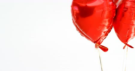 şeklinde : Red balloons floating in the air. Heart shaped balloons tied to string 4k