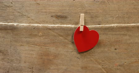 şeklinde : Red heart shaped  pinned on a string. Wooden wall in background 4k Stok Video