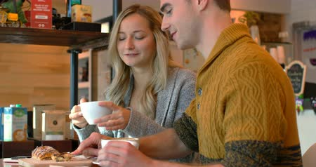 kobliha : Couple interacting with each other in cafe. Couple having coffee in cafe 4k Dostupné videozáznamy