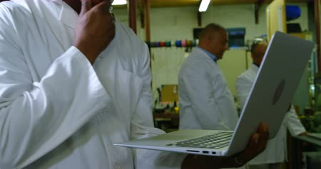 scrutiny : Worker using laptop in glass factory. Workers working in background 4k