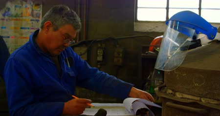 comprimento total : Male worker writing on clipboard in foundry workshop. Coworker standing in background 4k